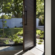 A floor to ceiling window sits alongside this architecture, door, home, house, window, wood, black
