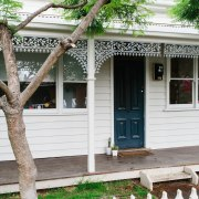 The Victorian facade has a farmhouse feel to backyard, cottage, facade, fence, home, house, outdoor structure, picket fence, plant, plantation, porch, property, real estate, residential area, shed, siding, structure, tree, window, yard, white