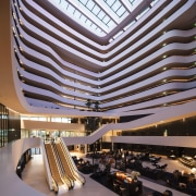 The interior looks like a layer cake, with architecture, building, ceiling, convention center, corporate headquarters, daylighting, headquarters, hotel, lobby, mixed use, performing arts center, shopping mall, black, purple