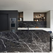 A marble island – part of the larger countertop, floor, flooring, interior design, kitchen, living room, property, real estate, black, gray