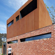 A Corten steel structure sits atop a brick architecture, brick, brickwork, building, commercial building, elevation, facade, house, real estate, residential area, siding, wall, red, teal