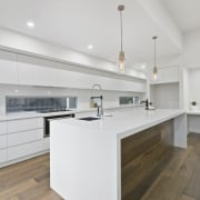 The wooden floor rises up and into the architecture, cabinetry, countertop, cuisine classique, floor, interior design, kitchen, property, real estate, room, gray