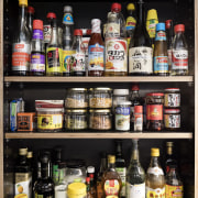 Easy access to condiments and spices alcohol, bottle, distilled beverage, drink, kitchen organizer, liquor store, product, shelf, black