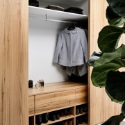 This spacious wardrobe has a dedicated spot for closet, furniture, room, shelf, shelving, wardrobe, orange