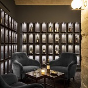 This new whiskey bar takes advantage of a chair, furniture, interior design, living room, lobby, wall, black