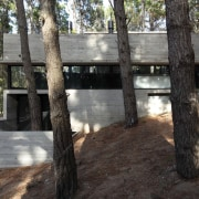 A sheltered outdoor area sits at the base architecture, house, tree, black, gray