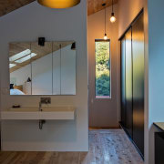 This bathroom has a view out to the architecture, ceiling, daylighting, floor, flooring, home, house, interior design, light fixture, lighting, room, wall, wood, wood flooring, gray, brown