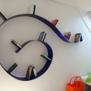 The bookcase almost looks as if it's about clock, furniture, product design, gray