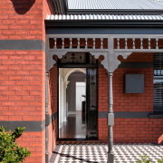 The front entrance retains many elements of the architecture, brick, building, facade, home, house, outdoor structure, porch, real estate, roof, window, red