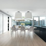 A large black kitchen island sits alongside the architecture, dining room, floor, flooring, house, interior design, interior designer, kitchen, white