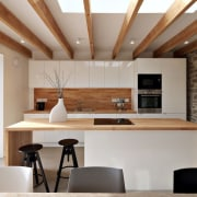 Wood accents tie this glossy white kitchen together architecture, ceiling, countertop, interior design, kitchen, table, gray, brown