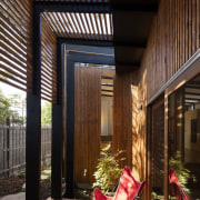 Wood slats filter the light in this outdoor architecture, courtyard, daylighting, facade, home, house, interior design, lighting, window, wood, black, brown