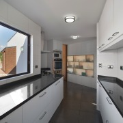 The narrow galley-style kitchen features translucent cupboards architecture, countertop, daylighting, interior design, kitchen, property, real estate, gray