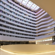 The lobby is expansive and light-filled thanks to architecture, building, condominium, corporate headquarters, daylighting, headquarters, hotel, mixed use, gray, orange
