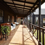 The covered deck runs alongside the home architecture, deck, estate, home, house, interior design, outdoor structure, patio, porch, property, real estate, roof, black