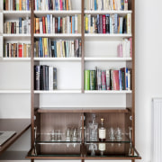 A liquor cabinet sits beneath this bookshelf in bookcase, furniture, library, public library, shelf, shelving, white