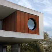 A porthole-esque window is perfect given the expansive architecture, building, facade, house, sky, black