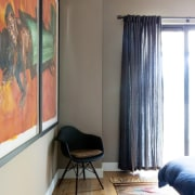 It's clear the owner loves his art curtain, floor, flooring, furniture, home, interior design, room, wall, window, window covering, window treatment, white, gray