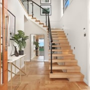 A unique staircase draws the eye when you architecture, daylighting, floor, flooring, handrail, hardwood, home, house, interior design, laminate flooring, property, real estate, stairs, wood, wood flooring, white, orange
