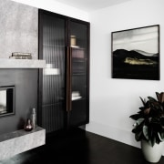 To the side of the fireplace, a storage door, floor, flooring, furniture, interior design, white, black