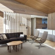 This living space sits at the centre of architecture, ceiling, daylighting, floor, flooring, furniture, house, interior design, living room, real estate, wall, wood, wood flooring, white, brown, gray