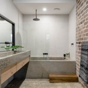 The concrete aesthetic continues throughout the home, including architecture, bathroom, countertop, floor, flooring, interior design, room, tile, wall, gray