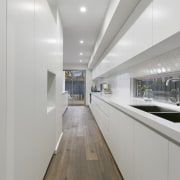 The long, white kitchen hides a scullery/work area interior design, real estate, gray