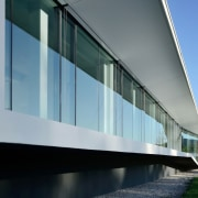 The east facade is a rectilinear and elongated architecture, building, corporate headquarters, daylighting, daytime, facade, glass, headquarters, house, sky, window, gray, teal