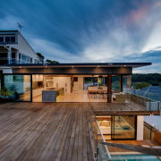 Submerged into a cliff face and featuring panoramic architecture, daylighting, deck, estate, home, house, property, real estate, roof, sky, swimming pool, villa, blue