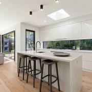 The kitchen flows into the living area countertop, cuisine classique, floor, flooring, hardwood, interior design, kitchen, real estate, wood flooring, gray