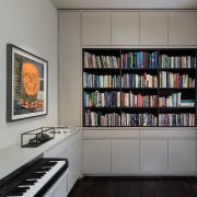 The library and study has a classical feeling bookcase, furniture, shelf, shelving, gray, black