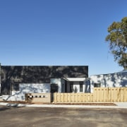 The tree line rises up above the development architecture, building, cottage, facade, home, house, property, real estate, residential area, teal