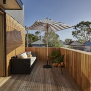 A wood deck and balustrade create a warm, backyard, balcony, deck, home, house, outdoor structure, property, real estate, roof, wood, brown
