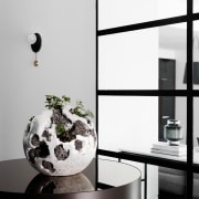 This centrepiece sits behind the living area black and white, furniture, glass, interior design, lamp, light fixture, monochrome, monochrome photography, product design, table, tap, white, black