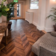 Herringbone patterns can give homes and commercial spaces floor, flooring, hardwood, home, interior design, laminate flooring, living room, real estate, tile, wood, wood flooring, brown, gray