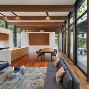 The dining, kitchen and living areas all share architecture, ceiling, house, interior design, living room, real estate, window, wood, gray, brown