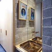 Exposed brick surrounds the brass sink bathroom, countertop, floor, flooring, interior design, room, tile, gray, white