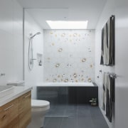 The bathroom features a large wet area architecture, bathroom, bathroom accessory, bathroom cabinet, ceiling, daylighting, floor, flooring, interior design, product design, room, sink, tile, wall, gray