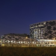 A unique facade covers the building architecture, building, city, corporate headquarters, landmark, metropolis, night, sky, structure, tourist attraction, tower block, blue, brown