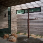 This outdoor shower is a beach necessity architecture, home, house, siding, wall, wood, black, gray