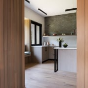 The kitchen sits slightly higher than the living architecture, cabinetry, door, floor, flooring, hardwood, house, interior design, laminate flooring, wall, wood, wood flooring, brown