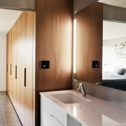 A bar light runs up the corner bathroom, bathroom accessory, cabinetry, countertop, floor, interior design, kitchen, room, sink, wood, gray, brown