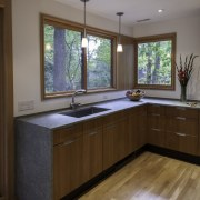 The countertop runs over and down to the cabinetry, countertop, floor, flooring, hardwood, home, interior design, kitchen, laminate flooring, real estate, room, sink, window, wood, wood flooring, gray, brown