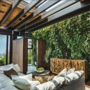 A green wall adds a unique touch to backyard, house, interior design, living room, outdoor structure, patio, real estate, roof, window, gray, black
