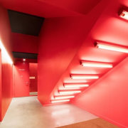 This unique lighting arrangement complements the red walls angle, apartment, architecture, ceiling, daylighting, floor, flooring, interior design, light, lighting, orange, red, stairs, wall, red, orange