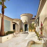 A private courtyard features potted plants and a courtyard, estate, hacienda, home, house, mansion, property, real estate, residential area, villa, orange
