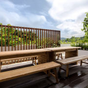 Greenery and seating abound bench, deck, furniture, outdoor furniture, outdoor structure, real estate, sunlounger, table, wood, white