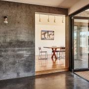 Concrete floors and walls give the home a door, floor, flooring, interior design, lobby, wall, window, wood flooring, brown