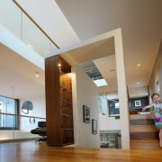A very happy occupant showcases the scale of architecture, ceiling, daylighting, floor, flooring, hardwood, home, house, interior design, lighting, living room, lobby, wood, wood flooring, brown, gray