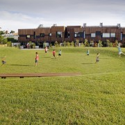 This development exists in a world of its campus, field, grass, grassland, land lot, landscape, lawn, leisure, meadow, pasture, plain, playground, public space, recreation, sky, sport venue, sports, team sport, yellow
